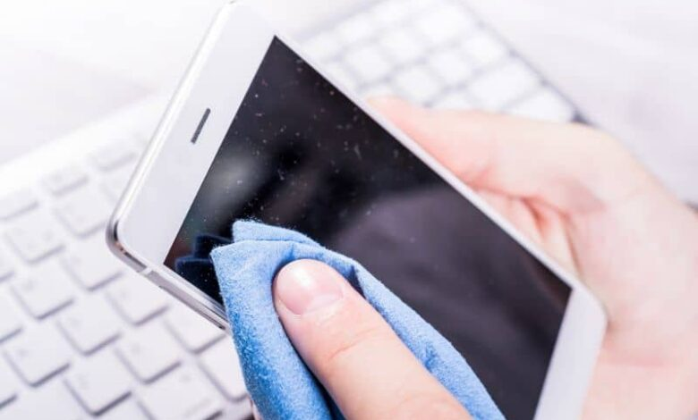 Hands cleaning the cell phone screen