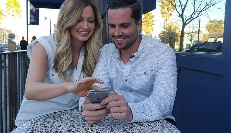 Couple laugh together watch mobile