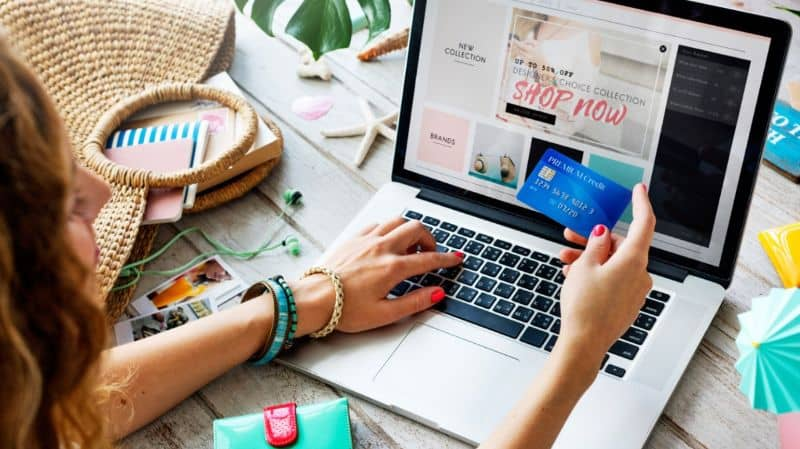 Woman doing online shopping with blue credit card in hand
