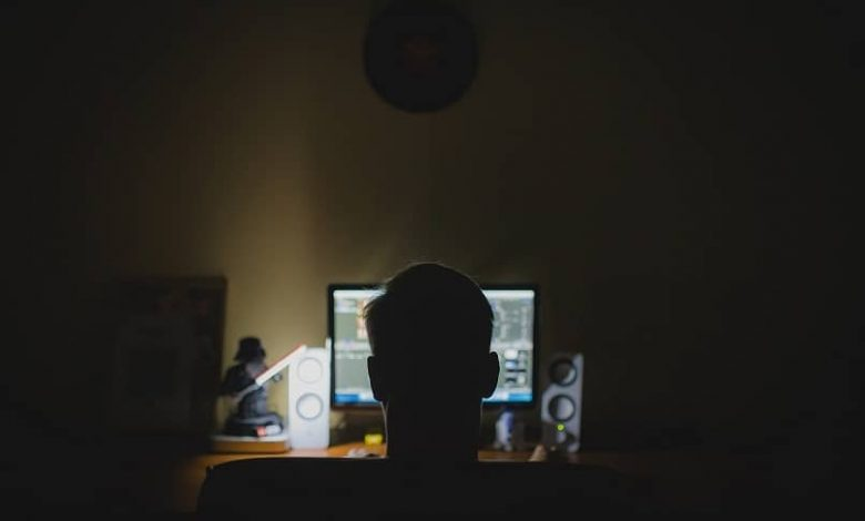 man looks at the monitor light in a dark room